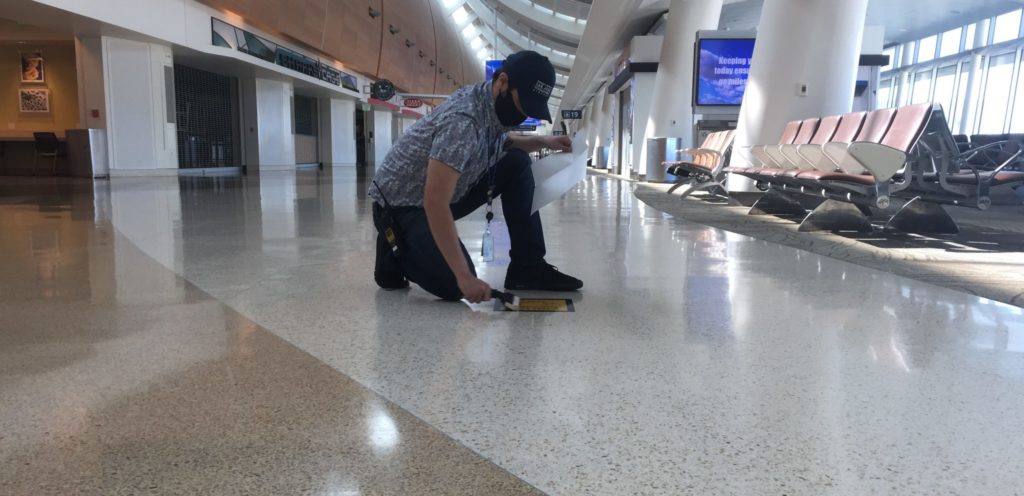 A worker at Norman Y. Mineta-San Jose International Airport cleans a social distancing floor sticker at one of the terminals. Photo courtesy of Norman Y. Mineta-San Jose International Airport.