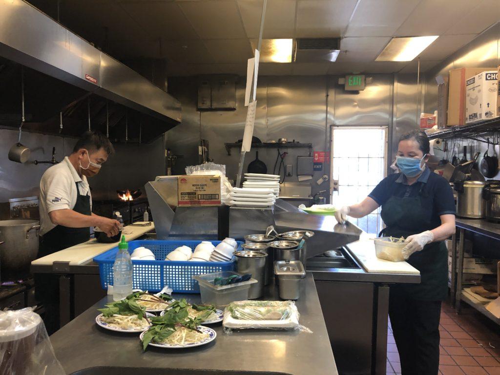 Heng và Huyền, hai nhân viên tại Phở Y # 1 Noodle House, chuẩn bị một món ăn trưa. Ảnh của Patricia Wei.