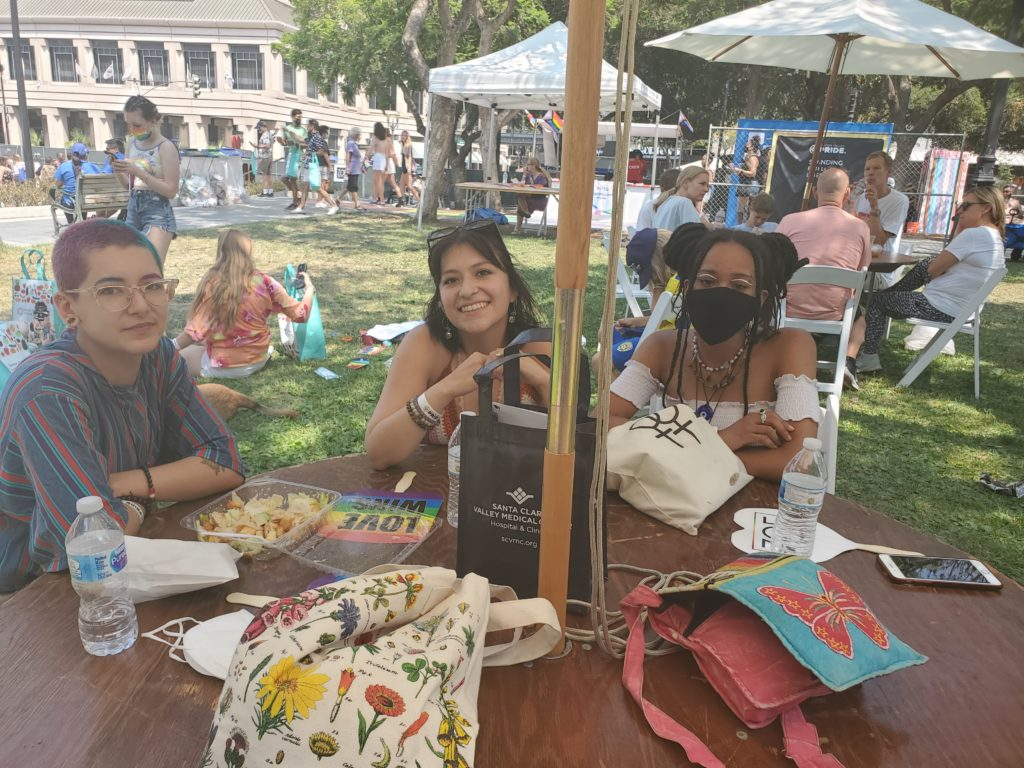 Three friends sit at a table at Silicon Valley Pride.